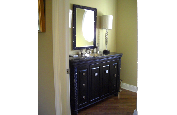 A vanity cabinet built around a black mirror with carved embossed square boxes and small mirrored square inlays.