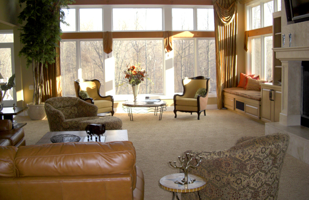 A large room overlooking a beautiful wooded back yard adapted into a comfortable space for watching television.